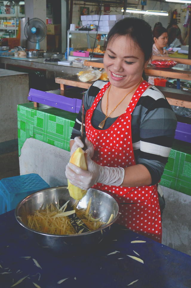 Woman slicing papaya | When in Chiang Mai: Fresh food markets | lizniland.com